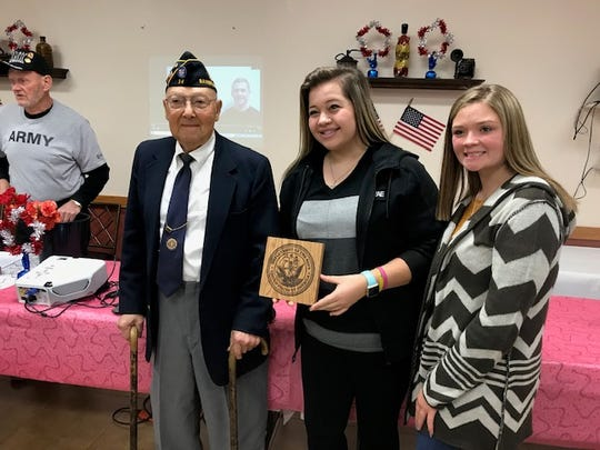 William Mcleary is presented with a plaque by Jadelyn Cochenour and Rylan Morrow from  the Pickaway-Ross Career & Technology Center at a ceremony at the Ross County Senior Center on Oct. 8, 2019.