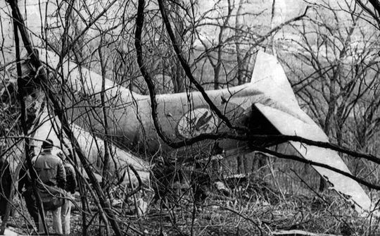 NOVEMBER 9, 1965: Screened by trees and huge vines, tail section of American Airlines jet plane is inspected today by officials on Northern Kentucky hillside where it crashed last night killing 58 persons. Four survived with serious injuries. Plane was approaching Greater Cincinnati Airport on flight from New York when it crashed in a rainstorm.