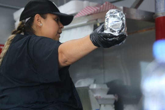 Fatboy Taco truck owner Diana Gonzalez hands off a burrito during their first day back in business after an accident in April.