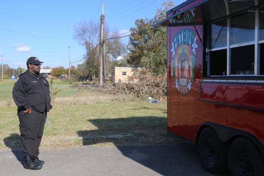 Shaleek Doe, a regular customer, waits for his order at the Fatboy Taco truck on their first day back in business after an accident in April.