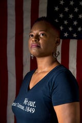 Monica Meeks, an Army veteran, poses for a portrait with the flag she was given at the time of her retirement from the Army at the Meeks household in Adams, Tenn., on Monday, Nov. 4, 2019.