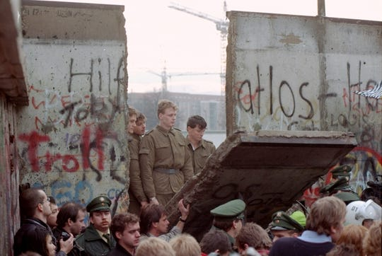 East German border guards look through a hole in the Berlin wall after demonstrators pulled down one segment of the wall at Brandenburg gate Saturday, November 11, 1989.