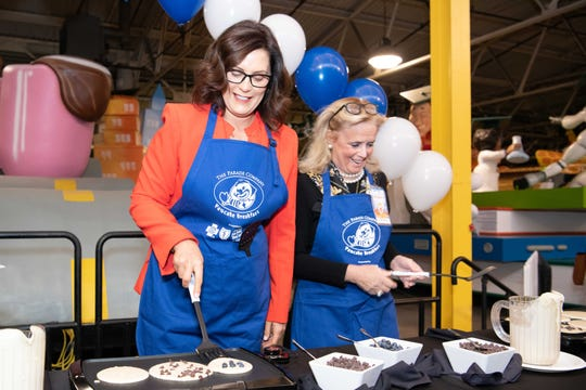 Gov. Gretchen Whitmer and U.S. Rep. Debbie Dingell make pancakes at Friday's Parade Company breakfast.
