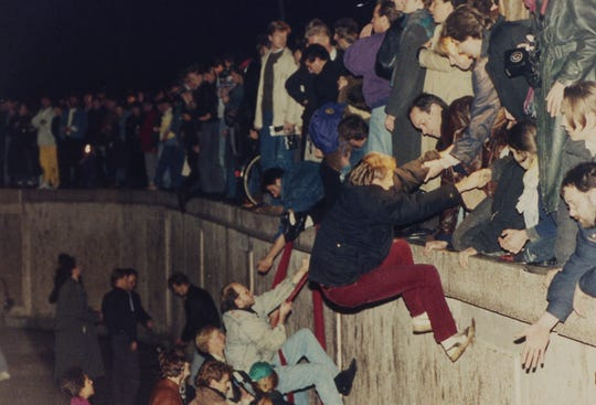 In this Nov. 10, 1989 file photo, East Berliners get helping hands from West Berliners as they climb the Berlin Wall which divided the city since the end of World War II, near the Brandenburger Tor (Brandenburg Gate).