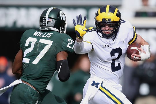 U-M's Shea Patterson tries to get around the tackle of MSU's Khari Willis at last year's Spartans-Wolverines game in East Lansing.