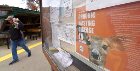 A firearms enthusiast walks past a Michigan DNR informational poster on Chronic Wasting Disease in the state.