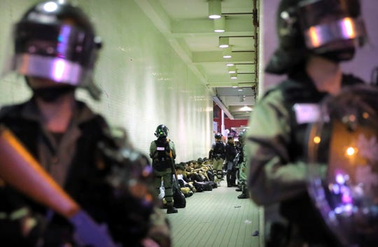 Police in riot gear stand over people detained during a protest in Hong Kong, Saturday, Nov. 2, 2019.
