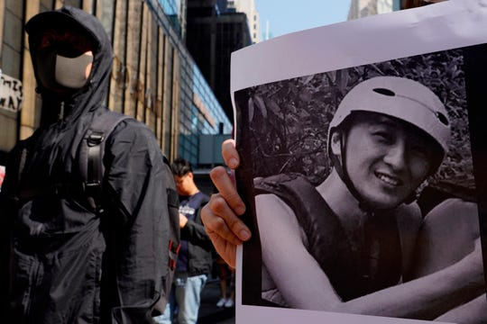 A protester stands near a photo of Chow Tsz-Lok during a memorial flash mob to remember him in Hong Kong on Friday.