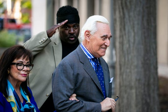 Roger Stone, and his wife Nydia, arrive as a man salutes him at Federal Court for his federal trial in Washington, Friday, Nov. 8, 2019.