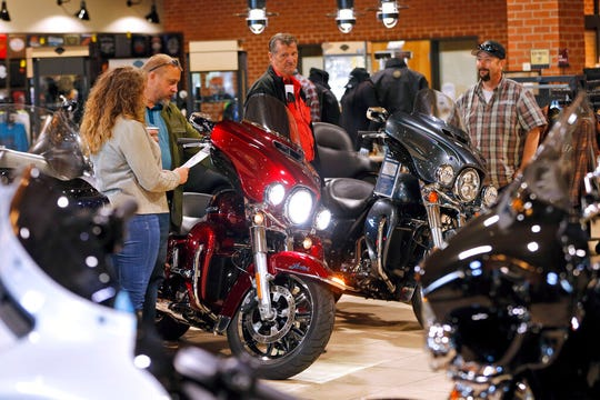 In this Oct. 17, 2019, file photo customers look over Harley Davidson motorcycles on display at a dealership in Ashland, Va. U.S. Consumer sentiment improved for a third-straight month in November as Americans grew more upbeat about their financial situation.