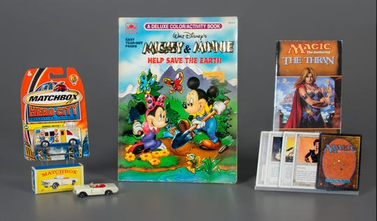 In this Oct. 7, 2019 photo provided by the National Toy Hall of Fame, Matchbox Cars, left, the coloring book, center, and the collectible card game Magic: The Gathering were inducted into the National Toy Hall of Fame in Rochester, N.Y.