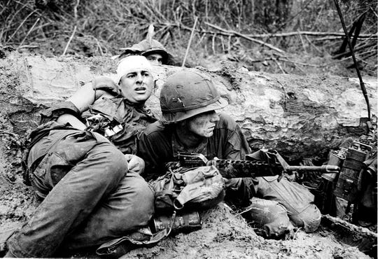 An American soldier is positioned over his rifle as he protects his wounded buddy during a battle against North Vietnamese in War Zone D near Phuoc Vinh, Vietnam, June 15, 1967.