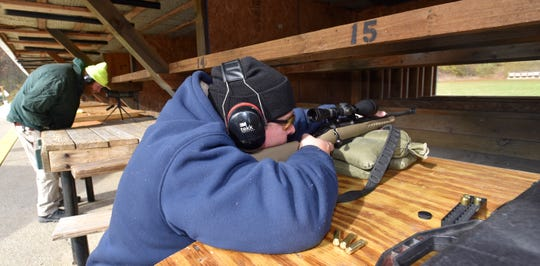 Deer hunter Brian Melonio of Highland Twp. shoots at a target 100 yards away as Michigan DNR Range Officer Josiah Clemence, left, looks at the target through a spotting scope Thursday at the Pontiac Lake Recreation Area Shooting Range.