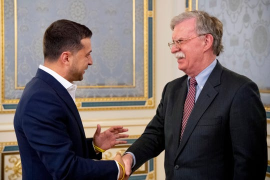 In this file photo taken on Aug. 28, 2019, John Bolton, U.S. National Security Advisor, right, is welcomed Ukrainian President Volodymyr Zelenskiy in Kyiv, Ukraine. Newly released transcripts reveal Bolton cut short a July meeting between White House and Ukrainian officials after Trump's envoy set out demands for investigations as the price of an Oval Office meeting for Zelenskiy.