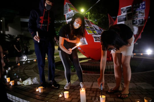 Students light candles to pay homage to Chow Tsz-Lok in Hong Kong on Friday. The ceremony was cut short, and black-clad masked students turned the stage into a memorial for Chow who fell off a parking garage after police fired tear gas during clashes with anti-government protesters.