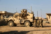 In this Feb. 23, 2017 photo, U.S. Army soldiers stand outside their armored vehicle on a joint base with Iraqi army south of Mosul, Iraq.  Iraqi security officials say 17 Katyusha rockets have hit an Iraqi air base south of the city of Mosul that houses American troops.