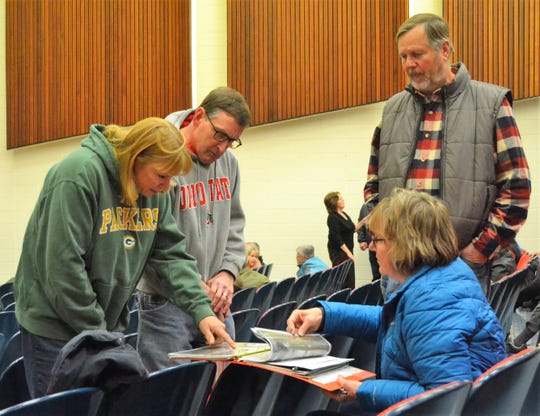 Frances Frye, seated, shows neighbors Nancy and John Holzberger pictures of property along Green Bay she took afterit was flooded on Oct. 21. At right is Frye's husband, Mark Stoeger. They were all among more than 150 people who attended a public meeting at Oconto High School Wednesday night during which federal, state and local officials discussed the flooding along the bay and related regulations.