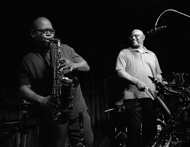 Gerald Smith, right, smiles as saxophonist Benjamin Hampton takes a solo while performing with The Jazzsmith's at a recent show at Blues Boulevard in downtown Greenville.