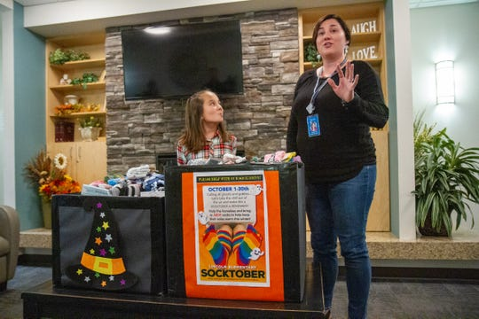 """Reia Henry, left, a fifth grade student at Lincoln Elementary School, presents Carrie Matter, right, the Development Director for the Great Falls Rescue Mission 834 pairs of socks that she collected for a project called """"Socktober."""" The socks will be given as gifts to families and individuals sponsored by the Great Falls Rescue Mission this holiday season."""