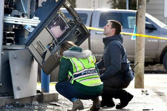 Police officers investigate an automated teller machine that exploded at the First Security Bank in Missoula, Mont., Thursday, Nov. 7, 2019.  A man has been charged in connection with the explosion.