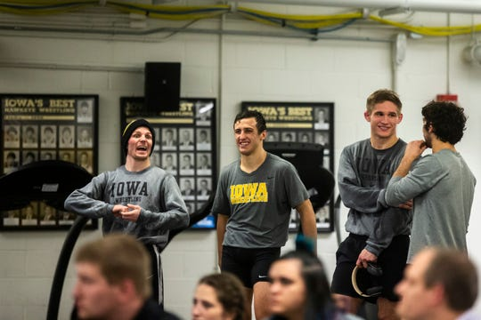 Former Hawkeye wrestler Cory Clark, left, busts a gut while current Hawkeye fifth-year wrestlers (from left) Michael Kemerer, Cash Wilcke and Vince Turk join the conversation during Iowa's wrestle-offs in November.