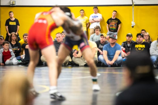 Iowa head coach Tom Brands, far left in background, watches as Vince Turk, red, wrestles Pat Lugo during the second day of preseason Hawkeye wrestling matches, Friday, Nov., 8, 2019, inside the Dan Gable Wrestling Complex at Carver-Hawkeye Arena in Iowa City, Iowa.