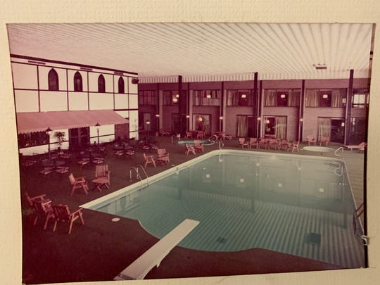 A view of The Highlander's indoor pool and sitting area. On both ends of the pool, hotel rooms overlook the water.