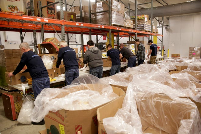 Volunteers sort donated frozen meats at the Food Finders Food Bank Warehouse, Friday, Nov. 8, 2019, in Lafayette.
