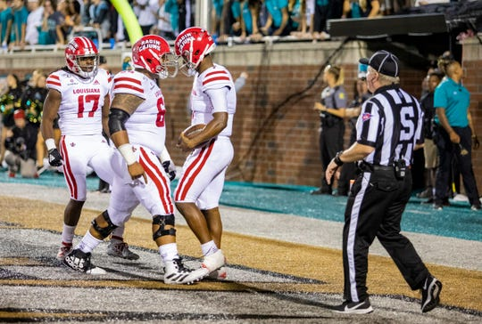 "UL receiver Jarrod ""Bam"" Jackson (left), center Shane Vallot (middle) and quarterback Levi Lewis celebrate Lewis' touchdown in last week's win at Coastal Carolina. The Ragin' Cajuns received one vote in this week's USA Today Top 25 coaches poll."