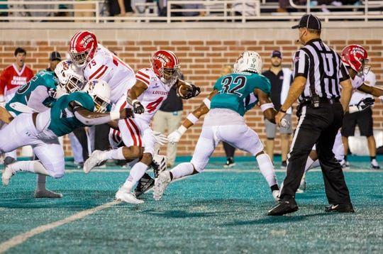 Tampa Bay Buccaneers draft choice Raymond Calais Jr. runs the ball for UL as Pittsburgh Steelers pick Kevin Dotson (75, left) blocks on the back side during a game last season at Coastal Carolina.