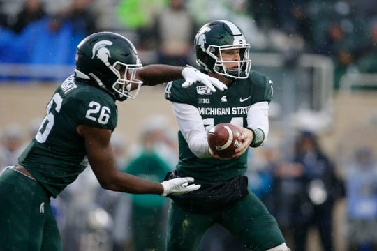 Michigan State quarterback Brian Lewerke, right, hands off to Brandon Wright against Penn State during the second quarter of an NCAA college football game, Saturday, Oct. 26, 2019, in East Lansing, Mich. Penn State won 28-7. (AP Photo/Al Goldis)
