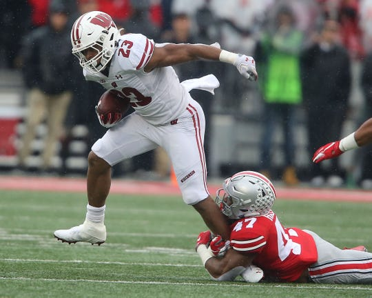 A serious Heisman Trophy contender until he ran into the Buckeyes, Wisconsin running back Jonathan Taylor can't elude the grasp of Ohio State linebacker Justin Hilliard.