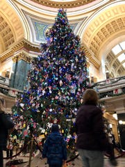 A child looks at the evergreen in the Wisconsin State Capitol on Dec. 22, 2018. The tree that sits in the Capitol rotunda during November and December will again be called a Holiday Tree, Gov. Tony Evers announced, but Republican legislators in the Assembly passed a resolution to call it a Christmas tree instead.