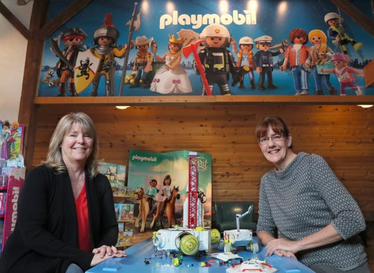 The Smiley Barn in Delafield has a full line showroom of Playmobil toys.  Here the owner of the Smiley Barn, Maria Luther, right, and general manager Mary O'Malley sit at a play table with a display of a spaceship and space station Playmobil set.