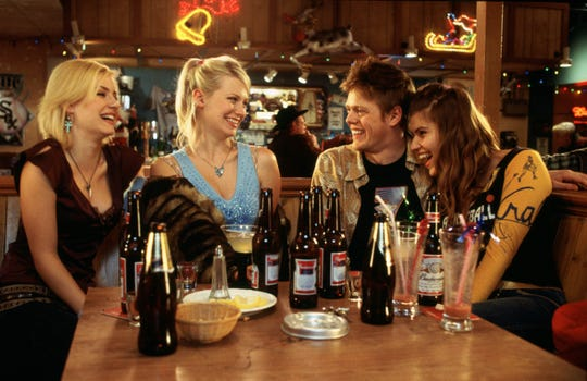 """Unlucky in love in England, a working-class bloke (Kris Marshall, second from right) heads to, of all places, Milwaukee to find romance in """"Love Actually."""" His new friends in this Milwaukee bar are played by, from left, Elisha Cuthbert, January Jones and Ivana Milicevic."""