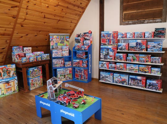 The Smiley Barn's Playmobil showroom includes a floor display of a fire station that kids can play with, near a wall lined with various trucks and related heavy equipment sets.