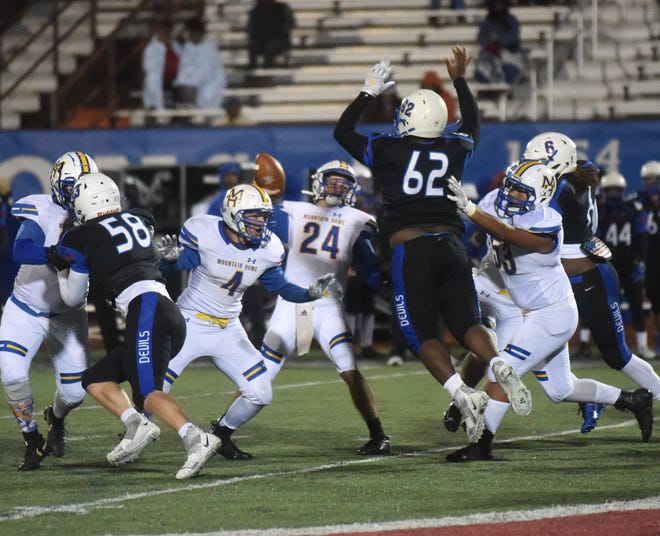 Mountain Home quarterback Lawson Stockton throws a pass over West Memphis' Kalon Prackett (62) as Bombers Dylan Poush, Tatem Beshears and Vin Le block on Thursday night.