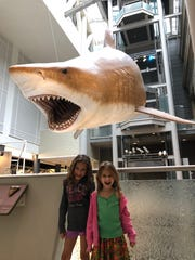 Ruby and her younger sister Juliette pose for a picture with a Great White Shark.