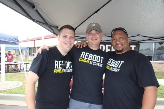 Reboot Recovery co-founder Evan Owens, left, attends a 2014 event with group leaders Bryan Flanery, center, and Erik Hampton.