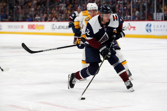 Colorado Avalanche right wing Joonas Donskoi, front, shoots the puck to score his third goal, after slipping past Nashville Predators center Kyle Turris during the third period of an NHL hockey game Thursday, Nov. 7, 2019, in Denver. Colorado won 9-4. (AP Photo/David Zalubowski)