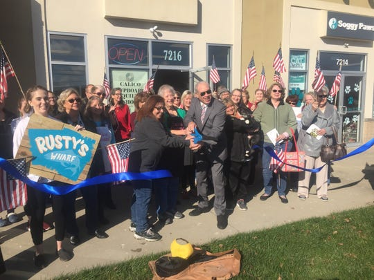 The ribbon is cut Nov. 8, marking the official opening of Rusty's Wharf, the Calico Cupboard and Soggy Paws in their new locations.