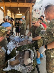 Dr. Robert Madlinger, a trauma surgeon,    assessing  a victim of an improvised explosive device (IED) at Forward Operating Base Fenty in Afghanistan. .