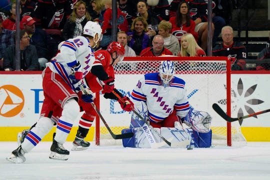 New York Rangers goaltender Henrik Lundqvist (30) stops a first period shot by Carolina Hurricanes right wing Andrei Svechnikov (37) at PNC Arena.