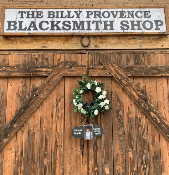 A sign and wreath hangs in memory of Billy Provence at his blacksmith shop at the New Mexico Farm & Ranch Heritage Museum.