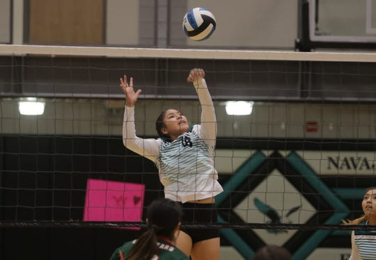 Navajo Prep's Caylynn Lee hits the ball over the net against Wingate during Thursday's District 1-3A volleyball tournament finals at the Eagles Nest in Farmington.