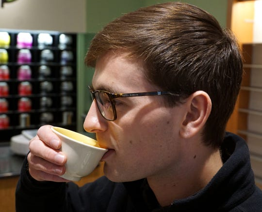 Visitors to Taste of Tea can sample some warm brew while they shop. Here Cody Wallace tries a cup of green tea.