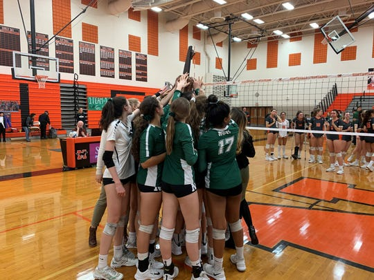 The Novi girls volleyball team celebrates its district championship win over Northville on Nov. 7, 2019.
