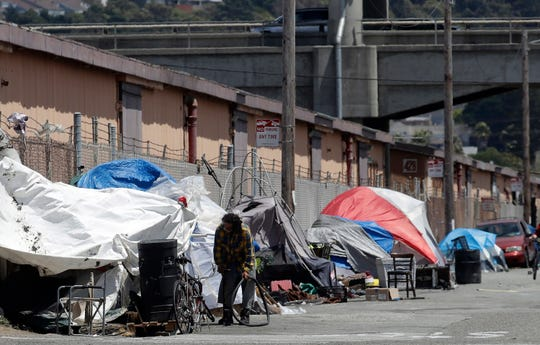 This June 27, 2019, file photo shows a man holding a bicycle tire outside of a tent along a street in San Francisco. Apple said Monday, Nov. 4, that it's committing $2.5 billion to combat California's housing crisis.