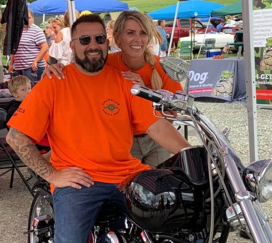 Michael Conrad, left, donated his Harley-Davidson motorcycle to Roots for Boots. The organization is led by Christy Lucas, pictured here.