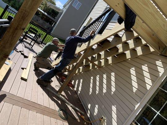 Eric Beaudoin, left, and Scott Lucas from Roots for Boots build stairs for Michael Conrad's new double-decker deck.